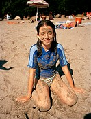 Girl covered in sand at beach