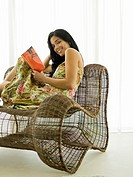 Woman reading in wicker chair