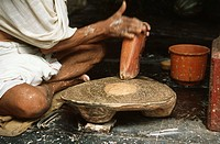 Indian priest preparing making god´s chandan tika sandalwood paste on pooja puja