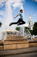 School boy jumping off fountain in center plaza