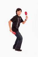 Studio portrait of young man dancing with maracas