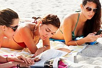 Women reading magazines and sunbathing on beach