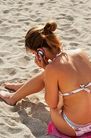 Young woman on cell phone at beach