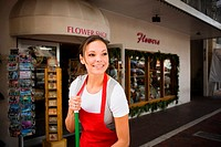 Young woman sweeps outside flower shop
