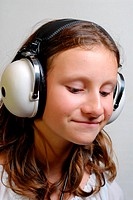 Smiling young girl listening to music on large headphones