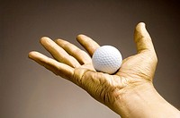Golden hand holding golf ball