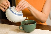 Woman pouring tea into teacup