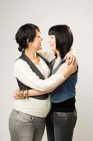Two women posing - a young adult and a pregnant woman
