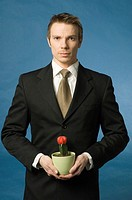 Businessman holding cactus in a pot