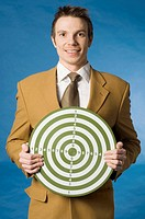 Businessman holding a dart board