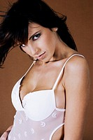 Woman in transparent white lingerie staring at the camera (thumbnail)