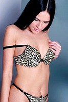 Woman in leopard print lingerie with bra strap falling off the shoulders
