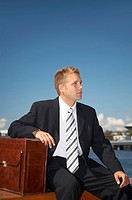 Businessman sitting outdoors with arm on briefcase