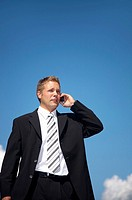 Businessman talking on the mobile phone outdoors (thumbnail)