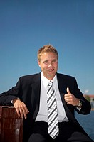 Businessman sitting outdoors with briefcase, showing thumbs up