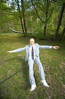 Businessman sitting on tightrope
