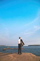 Businessman holding coat while enjoying the sea view