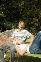 Man sitting on the bench with his girlfriend lying on his lap