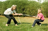 Grandmother and granddaughter playing tug of war