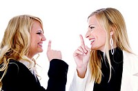 Businesswomen smiling while showing hushing sign to each other