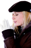 Woman in winter clothing closing her eyes