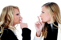 Two businesswomen showing hushing sign while looking at each other