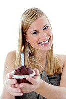 Woman smiling at the camera while holding birthday cake