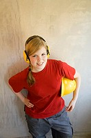 Teenage girl with ear protectors holding safety helmet