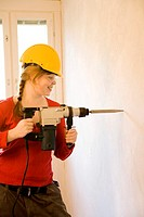 Woman drilling the wall