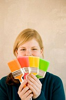 Young woman with colourful paint brushes