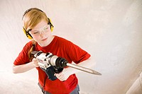 Teenage girl with ear protectors using drill