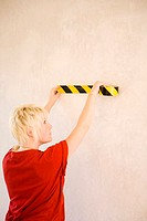 Woman taping the wall with an adhesive tape