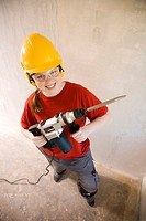 Teenage girl smiling while holding drill (thumbnail)