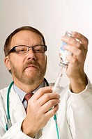 Doctor extracting fluid with a syringe from medicine bottle