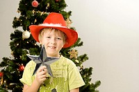 Boy standing in front of Christmas tree holding a tree-topper (thumbnail)