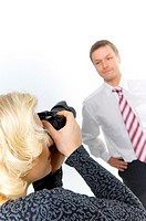 Woman taking photograph of businessman in the studio (thumbnail)