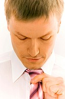 Close-up of businessman adjusting his necktie (thumbnail)