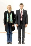 Businessman and businesswoman standing at attention with their eyes closed
