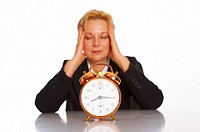 Alarm clock with businesswoman sitting and holding her temples in the background