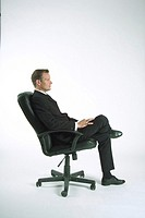 Businessman sitting on office chair, side view