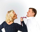 Angry woman pulling businessman's tie