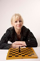 Businesswoman posing in front of chess game