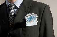 Midsection of businessman with money in his blazer pocket