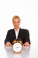 Alarm clock with businesswoman sitting in the background