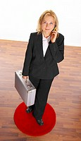 Businesswoman holding a briefcase and mobile