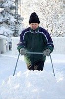 Old man removing snow with snow cleaner
