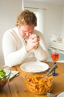 Man praying before having his meal