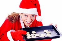 Woman holding freshly baked cookies in a tray
