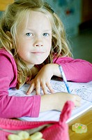 Girl smiling at camera while doing her homework