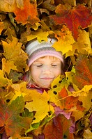 Girl with autumn leaves covering her (thumbnail)